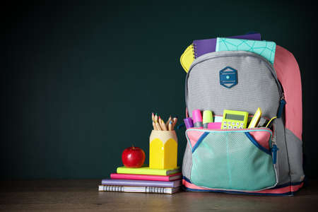 Stylish backpack with different school stationery on table against chalkboard. Space for text