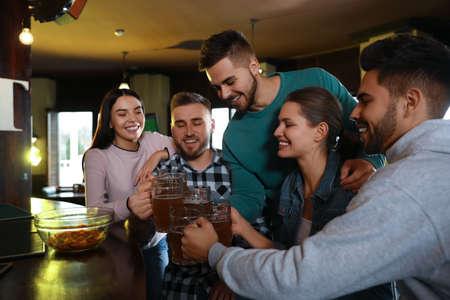 Group of friends celebrating victory of favorite football team in sport bar Foto de archivo
