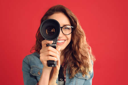Beautiful young woman with vintage video camera against red background, focus on lens
