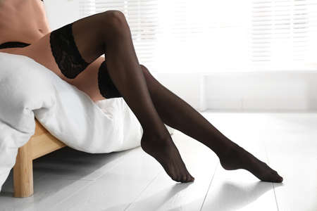 Young woman wearing stockings in bedroom, closeup