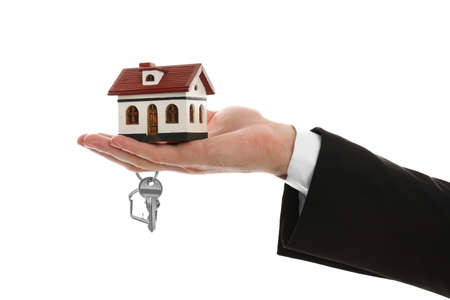 Real estate agent holding house model and key on white background, closeup