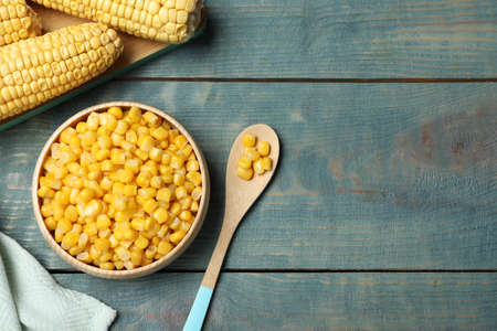 Tasty canned sweet corn on blue wooden table, flat lay. Space for text Banco de Imagens