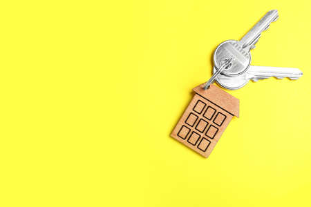 Keys with trinket in shape of house on yellow background, top view and space for text. Real estate agent services