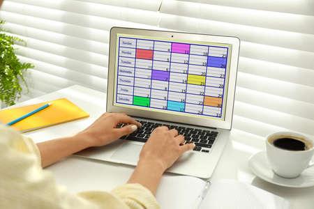 Junge Frau mit Kalender-App auf Laptop im Büro, Nahaufnahme Standard-Bild