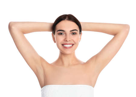 Young woman showing hairless armpits after epilation procedure on white background
