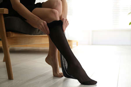 Young woman putting on tights at home, closeup Stock Photo