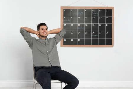 Handsome man sitting near board calendar indoors