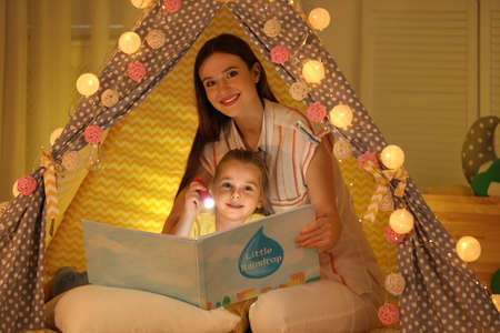 Mother and daughter with flashlight reading book in play tent at home