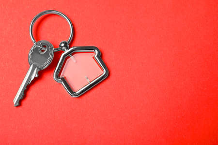 Key with trinket in shape of house on red background, top view and space for text. Real estate agent services