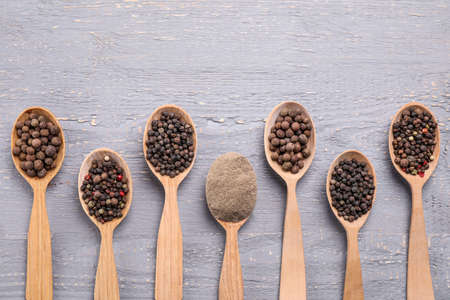 Ground pepper and corns on grey wooden table, flat lay Stockfoto