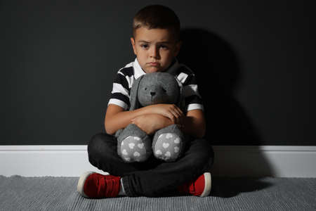 Sad little boy with toy near black wall. Domestic violence concept