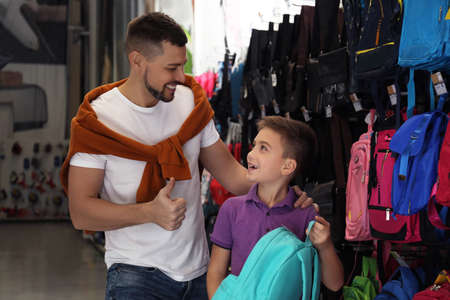 Little school boy with father choosing backpack in supermarket