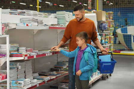 Little boy and father choosing school stationery in store