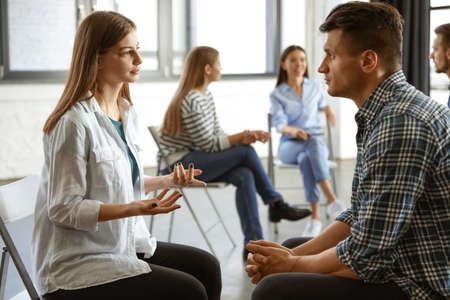 Psychotherapist working with patient in group therapy session indoors