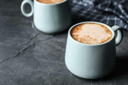 Tazas de delicioso chocolate caliente en mesa gris. Espacio para texto