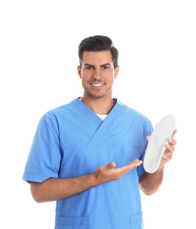 Male orthopedist showing insole on white background