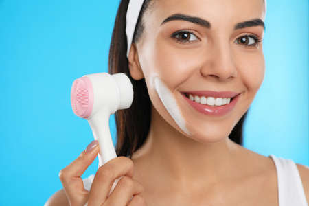 Young woman using facial cleansing brush on light blue background, closeup. Washing accessory