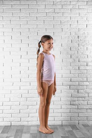 Jolie petite fille en sous-vêtements près du mur de briques blanches