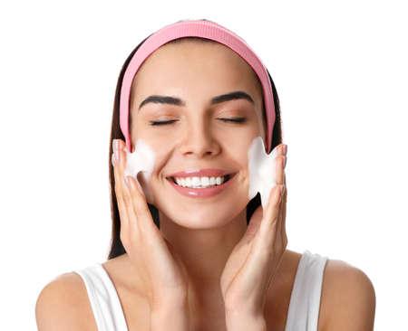 Jeune femme appliquant un produit cosmétique sur fond blanc. Routine de lavage