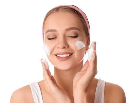Jonge vrouw wassen gezicht met reinigingsschuim op witte achtergrond. Cosmetisch product