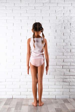 Petite fille en sous-vêtements près du mur de briques blanches, vue arrière
