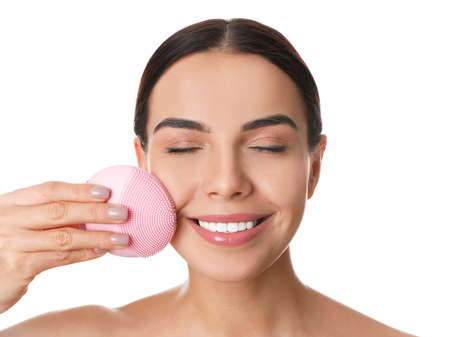 Young woman using facial cleansing brush on white background. Washing accessory Banque d'images