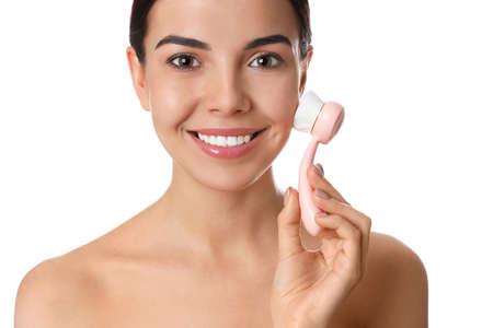 Jonge vrouw die gezichtsreinigingsborstel op witte achtergrond gebruikt. Wasaccessoire