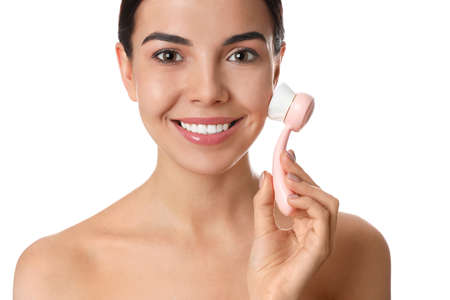 Young woman using facial cleansing brush on white background. Washing accessory