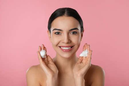 Jeune femme appliquant un produit cosmétique sur fond rose. Routine de lavage