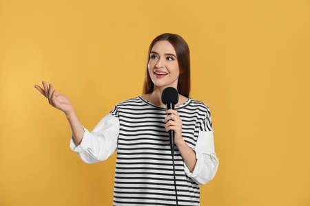 Giovane giornalista femminile con microfono su sfondo giallo Archivio Fotografico