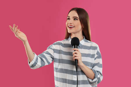 Young female journalist with microphone on pink background