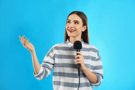 Young female journalist with microphone on blue background 免版税图像