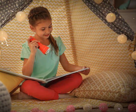 Little girl with flashlight reading book in play tent