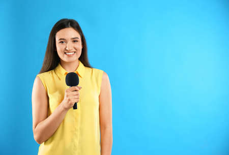 Young female journalist with microphone on blue background. Space for text