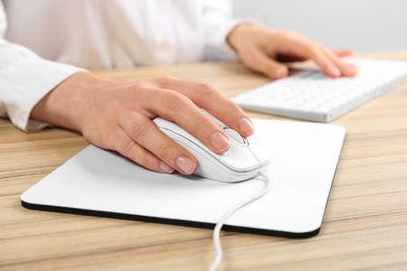 Femme à l'aide d'une souris optique filaire moderne à la table de bureau, gros plan