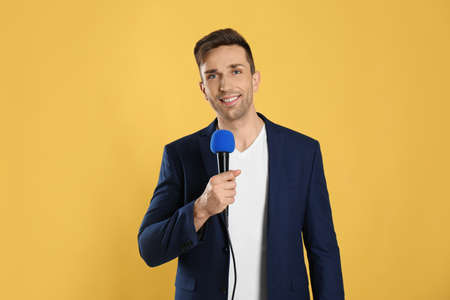 Young male journalist with microphone on yellow background