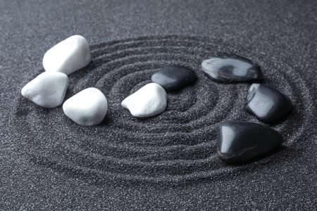 Stones on black sand with beautiful pattern. Zen and harmony