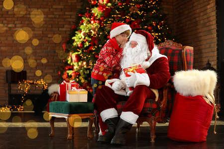Weihnachtsmann und kleiner Junge in der Nähe von Weihnachtsbaum drinnen Standard-Bild