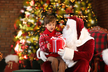 Santa Claus and little boy with gift near Christmas tree indoors