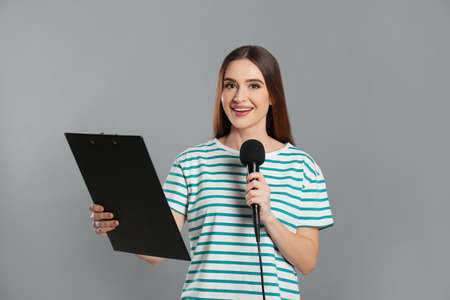 Young female journalist with microphone and clipboard on grey background Stok Fotoğraf