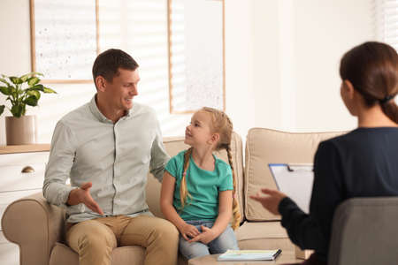Little girl and her father on appointment with child psychotherapist indoors 版權商用圖片