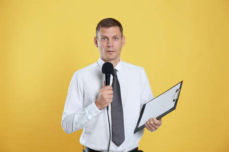 Male journalist with microphone and clipboard on yellow background