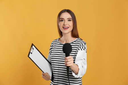 Young female journalist with microphone and clipboard on yellow background