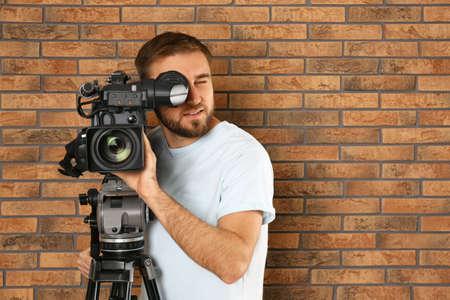 Operador con cámara de video profesional cerca de la pared de ladrillo, espacio para texto
