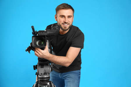 Operator with professional video camera on blue background