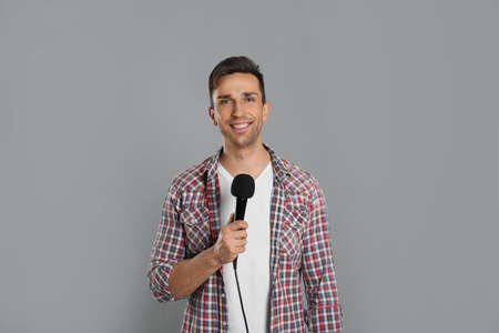 Young male journalist with microphone on grey background