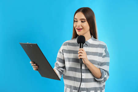 Young female journalist with microphone and clipboard on blue background