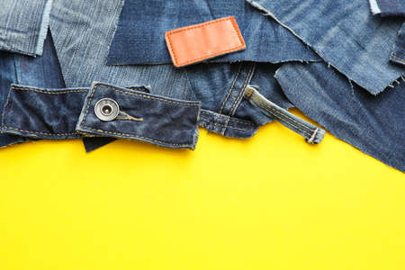 Flat lay composition with patches of old jeans on yellow background. Space for text