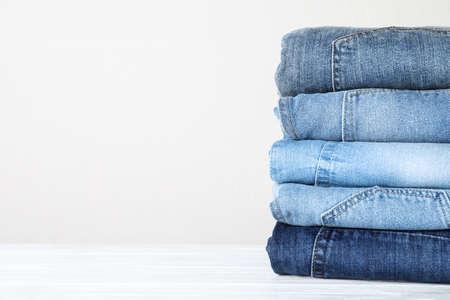 Stapel verschiedener Jeans auf weißem Holztisch. Platz für Text Standard-Bild