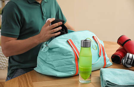 Man packing sports bag for training indoors, closeup